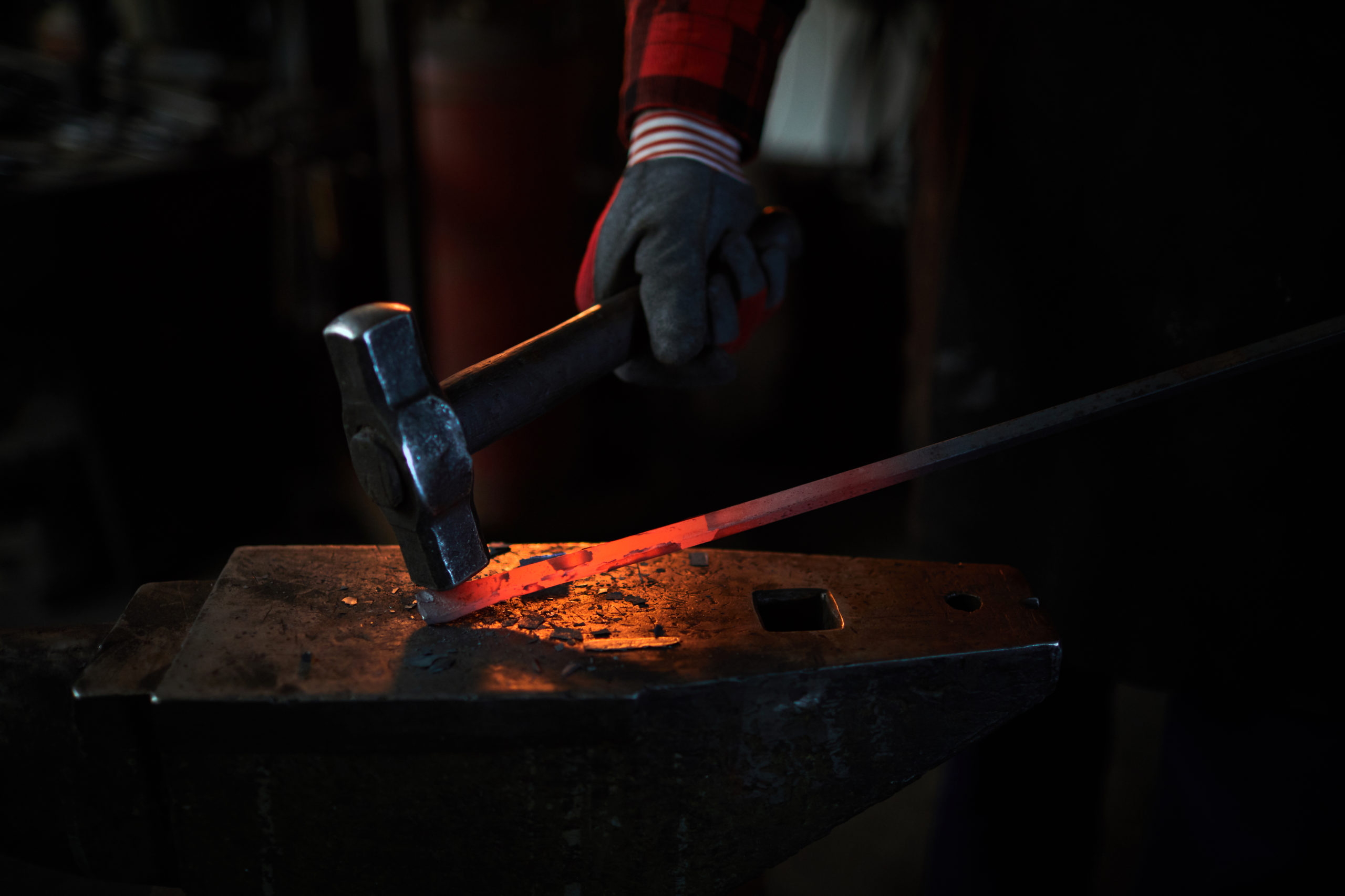Gloved hand of blacksmith with hammer during work with hot red iron workpiece
