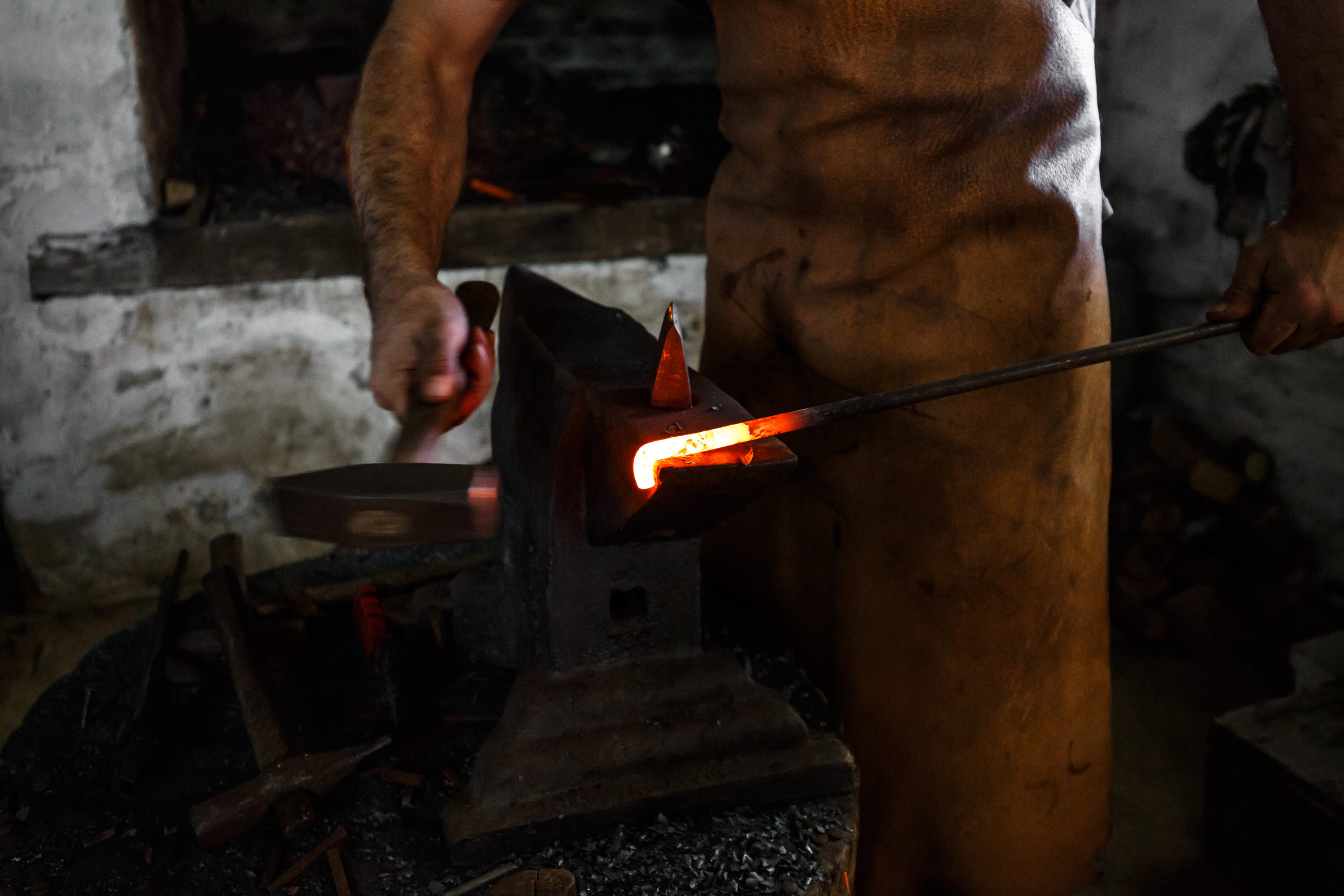 The blacksmith forge the hot metal on the anvil in smithy